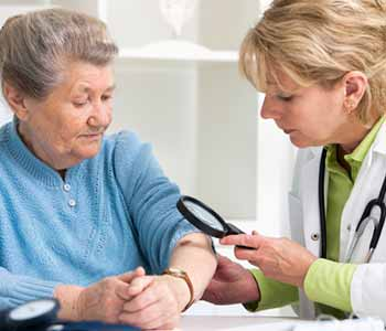 Image of an old woman checking her mark by a doctor