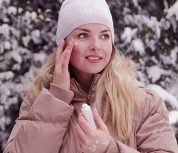 Woman applying skin cream on face and hands,protecting from cold weather on winter season