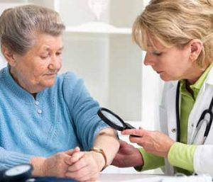 Senior woman checking her skin by a doctor